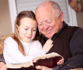 Grandfather reads the Bible to his granddaughter