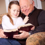 Grandfather reading Bible with his granddaughter